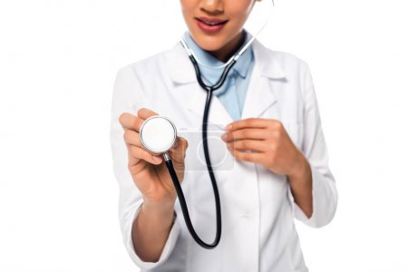 Photo pour Vue recadrée d'un médecin afro-américain montrant un stéthoscope isolé sur blanc - image libre de droit
