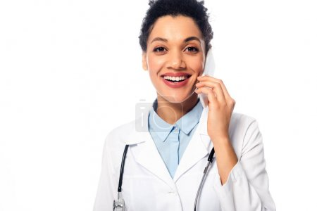 Front view of happy african american doctor with stethoscope talking on smartphone isolated on white