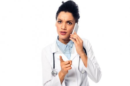 Photo for Front view of worried african american doctor with stethoscope talking on smartphone isolated on white - Royalty Free Image