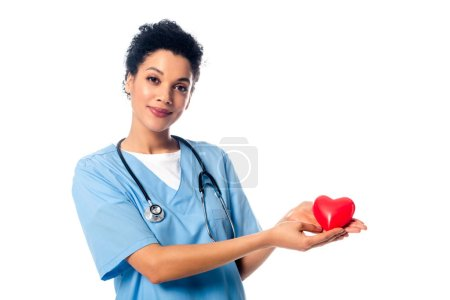Photo pour Infirmière afro-américaine avec stéthoscope montrant le coeur rouge décoratif regardant la caméra isolée sur blanc - image libre de droit