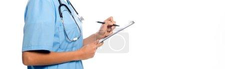 Photo pour Vue recadrée d'une infirmière afro-américaine écrivant sur un presse-papiers et souriant isolé sur une photo panoramique blanche - image libre de droit