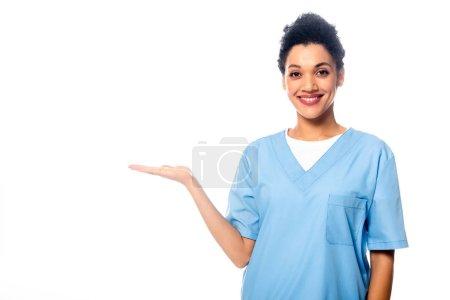 Photo pour Infirmière afro-américaine souriante et pointant avec la main isolée sur blanc - image libre de droit