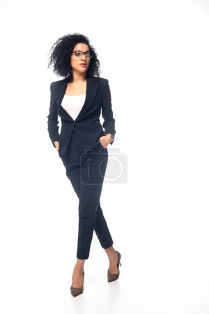 Photo pour Vue complète de la femme d'affaires afro-américaine confiante marchant avec les mains dans les poches sur fond blanc - image libre de droit