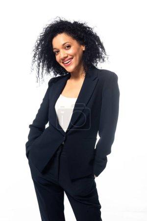 Photo pour Vue de face de femme d'affaires afro-américaine avec les mains dans les poches souriantes et regardant la caméra isolée sur blanc - image libre de droit