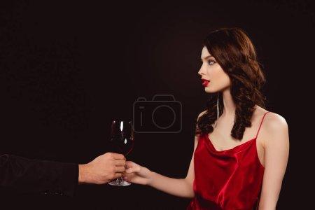 Photo pour Vue latérale de l'homme donnant un verre de vin rouge à une élégante fille isolée sur noir - image libre de droit