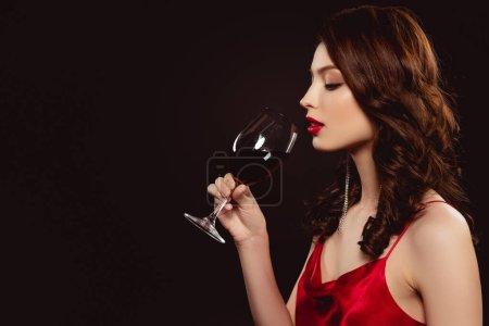 Photo pour Vue latérale de belle fille en robe élégante buvant du vin isolé sur noir - image libre de droit