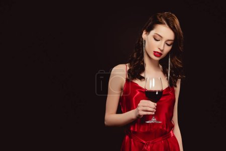 Photo for Elegant woman in red dress holding glass of wine isolated on black - Royalty Free Image