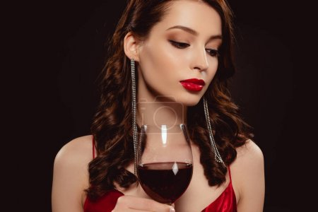 Photo pour Belle femme aux lèvres rouges tenant un verre de vin isolé sur noir - image libre de droit