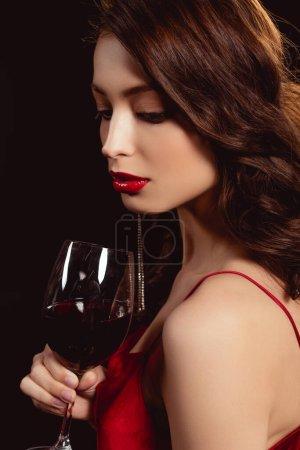 Photo pour Vue latérale d'une belle femme aux lèvres rouges tenant un verre de vin isolé sur du noir - image libre de droit
