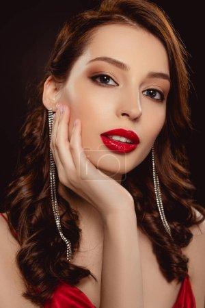 Photo pour Portrait de belle femme aux lèvres rouges touchant le visage et regardant la caméra isolée sur noir - image libre de droit