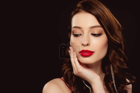Beautiful woman with red lipstick on lips touching face isolated on black