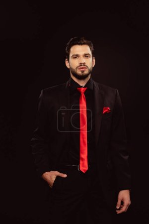 Handsome man in suit and red tie looking at camera isolated on black