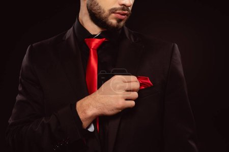 Photo for Cropped view of elegant man in suit adjusting handkerchief isolated on black - Royalty Free Image