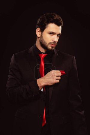 Elegant man in formal wear adjusting handkerchief and looking at camera isolated on black