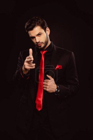 Photo for Handsome man in suit pointing with fingers and looking at camera isolated on black - Royalty Free Image