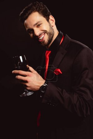 Photo for Handsome man in formal wear holding glass of red wine and smiling at camera isolated on black - Royalty Free Image