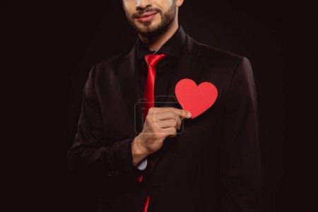 Photo pour Vue recadrée d'un homme élégant tenant du papier rouge en forme de coeur isolé sur du noir - image libre de droit