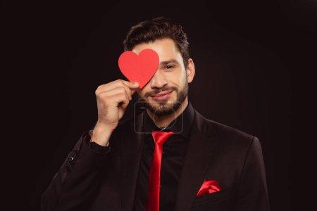 Photo pour Beau homme couvrant les yeux avec du papier en forme de coeur isolé sur noir - image libre de droit