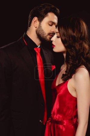 Photo pour Vue latérale d'un bel homme embrassant belle copine en robe isolée sur noir - image libre de droit