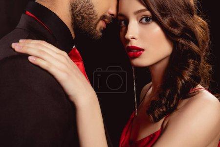 Photo pour Vue latérale de belle fille avec des lèvres rouges regardant la caméra tout en embrassant petit ami isolé sur noir - image libre de droit
