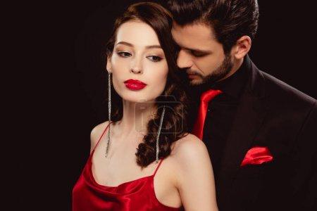Photo pour Belle femme debout près d'un bel homme en costume isolé sur noir - image libre de droit