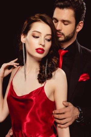 Photo pour Homme élégant embrassant belle femme en robe rouge isolé sur noir - image libre de droit