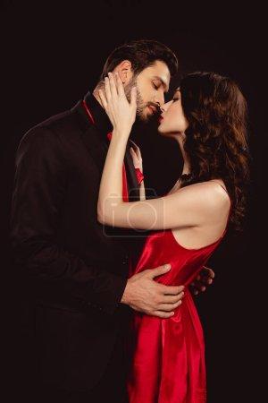 Photo pour Vue latérale d'une femme élégante en robe rouge baisant beau copain en costume isolé sur noir - image libre de droit