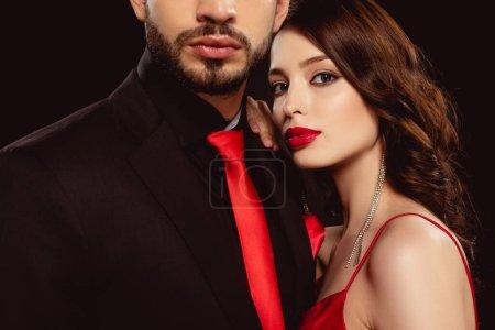 Photo pour Femme élégante avec des lèvres rouges regardant la caméra entendre petit ami dans l'usure formelle isolé sur noir - image libre de droit