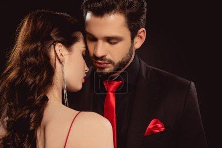 Photo pour Belle femme debout près de bel homme en tenue formelle isolé sur noir - image libre de droit
