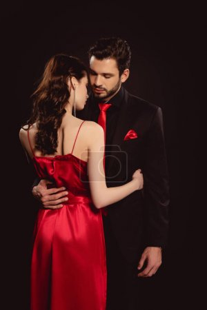 Handsome man in suit hugging by waist elegant girlfriend in red dress isolated on black