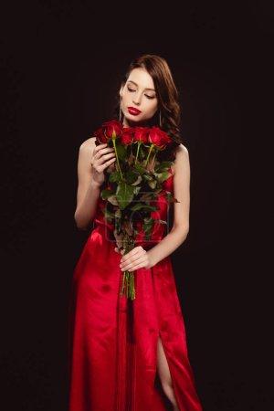 Photo pour Femme élégante en robe rouge tenant des roses isolées sur noir - image libre de droit