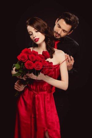 Photo pour Bel homme décoller robe de élégante petite amie avec des roses rouges isolé sur noir - image libre de droit