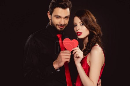 Elegant couple holding paper heart and looking at camera isolated on black