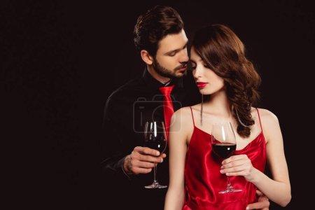 Photo pour Elégant homme embrassant belle copine avec un verre de vin rouge isolé sur noir - image libre de droit