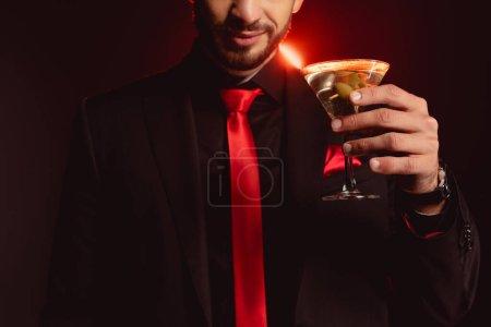 Ausgeschnittene Ansicht eines eleganten Mannes mit einem Glas Cocktail auf schwarzem Hintergrund mit Beleuchtung