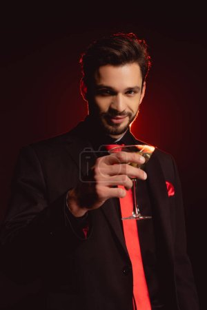 Photo for Handsome man in suit holding glass of cocktail on black background with lighting - Royalty Free Image