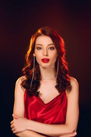 Photo pour Femme élégante en robe rouge regardant la caméra isolée sur noir - image libre de droit