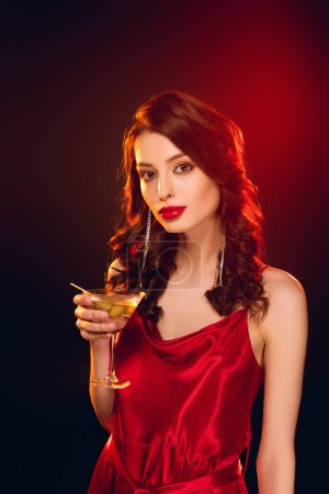 Beautiful woman in red dress holding glass of cocktail on black background with lighting