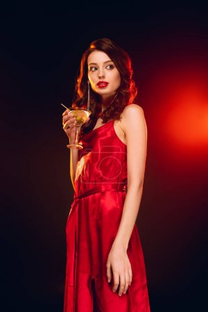 Photo for Elegant girl in red dress holding glass of martini on black background with lighting - Royalty Free Image