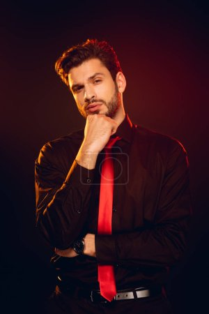 Photo for Elegant man in formal wear with hand near chin looking at camera on black background with lighting - Royalty Free Image
