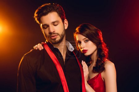 Photo for Elegant girl embracing handsome boyfriend with untied tie on black background with lighting - Royalty Free Image