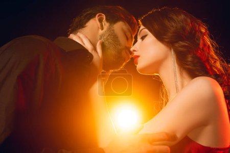 Photo pour Vue à angle bas d'une femme élégante embrassant son beau copain sur fond noir avec éclairage - image libre de droit