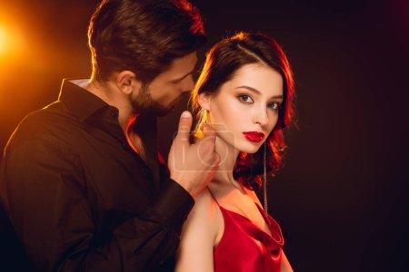 Photo pour Vue latérale d'un bel homme touchant le cou d'une belle petite amie regardant la caméra sur fond noir avec éclairage - image libre de droit