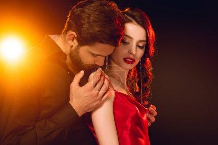 Photo pour Vue latérale de bel homme décollant robe de belle femme sur fond noir avec éclairage - image libre de droit