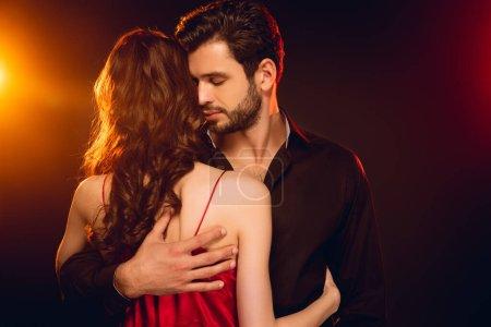 Photo pour Beau homme embrassant sa petite amie en robe rouge sur fond noir avec éclairage - image libre de droit