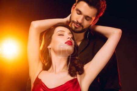 Foto de Elegante chica abrazando a un novio guapo sobre fondo negro con iluminación. - Imagen libre de derechos