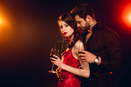 Photo for Side view of woman holding glass of wine near elegant boyfriend on black background with lighting - Royalty Free Image