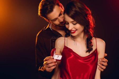 Photo pour Beau homme tenant une boîte-cadeau avec une bague à bijoux et une petite amie souriante sur fond noir avec éclairage - image libre de droit