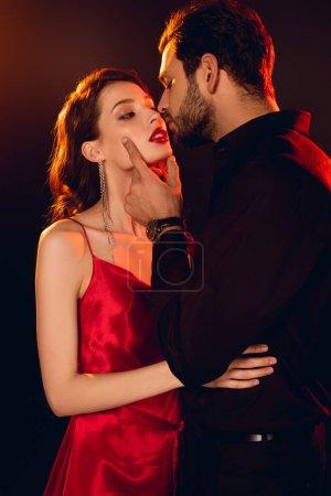 Photo pour Beau homme embrassant élégante copine aux lèvres rouges isolées sur noir - image libre de droit