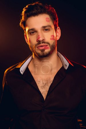 Photo for Handsome man with lipstick prints on face looking at camera isolated on black - Royalty Free Image